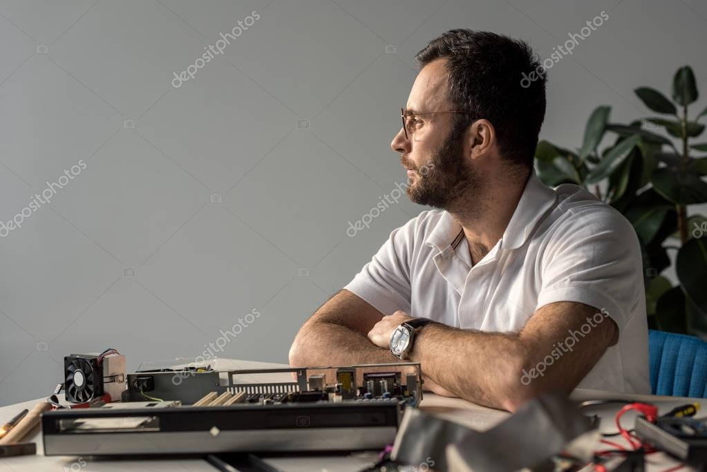 man with hands on table against pc looking away