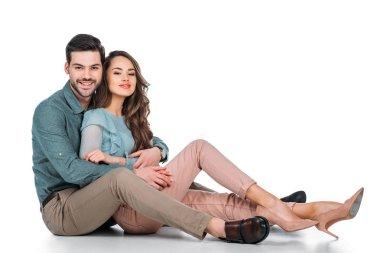 beautiful happy couple sitting on floor on white