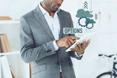 Fotografie cropped image of african american man using digital tablet and options graphic