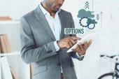 Fotografie abgeschnittenes Bild eines afrikanisch-amerikanischen Mannes mit digitalem Tablet und Optionsgrafik