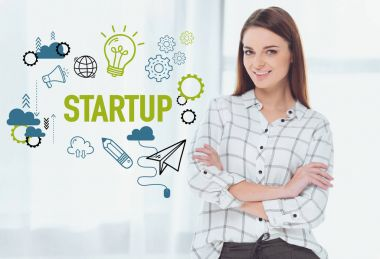 attractive businesswoman standing with crossed arms and looking at camera, startup concept