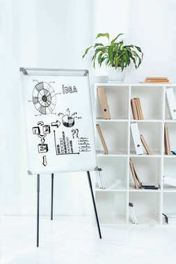 whiteboard with business idea icons and wooden shelves with folders in office