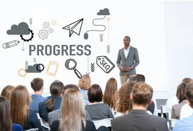 african american man standing near progress icons at meeting