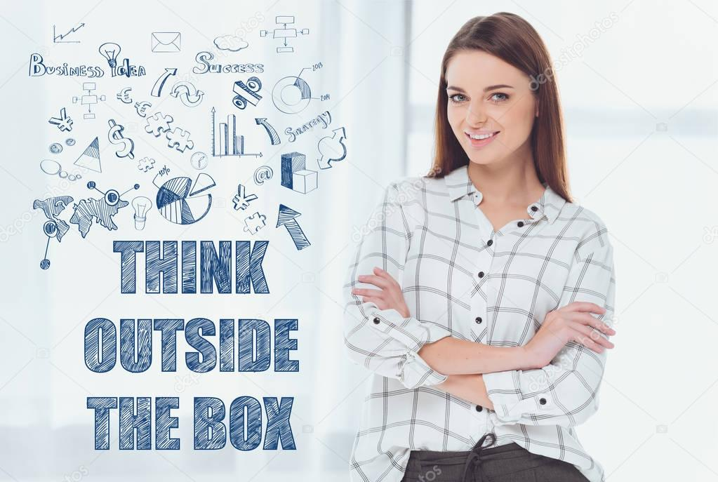 attractive businesswoman standing with crossed arms and looking at camera, inscription think outside the box