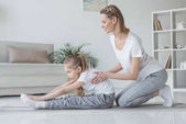 Photo mother helping her daughter to do forward bend at home