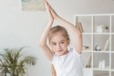 adorable little child practicing yoga and making namaste gesture