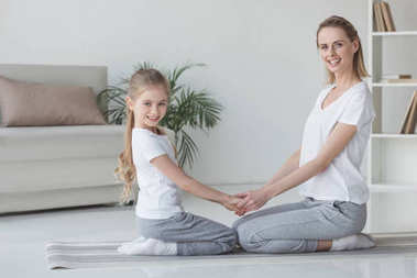 mother and daughter standing on knees and holding hands