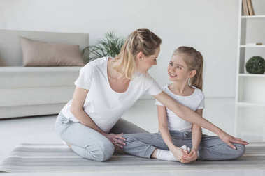 mother teaching daughter how to sit in yoga butterfly pose