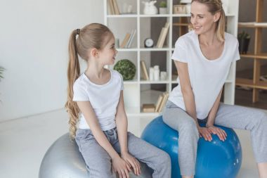 happy mother and daughter sitting on fit balls at home and looking at each other