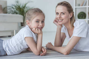 mother and daughter lying on floor together and looking at camera