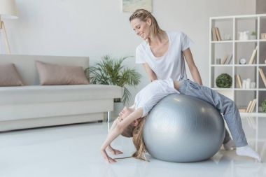 mother teaching her daughter to stand in yoga wheel pose with fit ball
