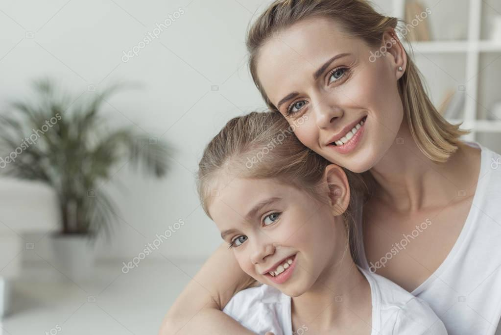 Close-up portrait of mother and daughter embracing at home stock vector