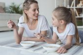 happy mother and daughter eating cereal meal while lying on yoga mats