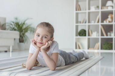 smiling little child lying on yoga mat and looking at camera