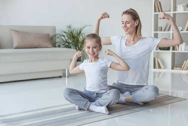 mother and daughter showing muscles on yoga mats