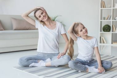 mother and daughter stretching neck before exercising at home