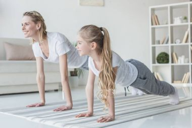 mother and daughter doing plank exercise on yoga mats