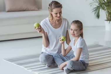 happy mother and daughter eating apples on floor