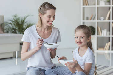 mother and daughter eating cereal meal while sitting on floor
