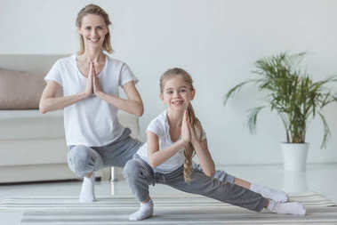 mother and daughter practicing yoga together at home