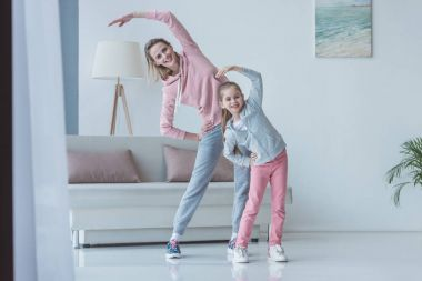 fit mother and daughter doing side bends at home