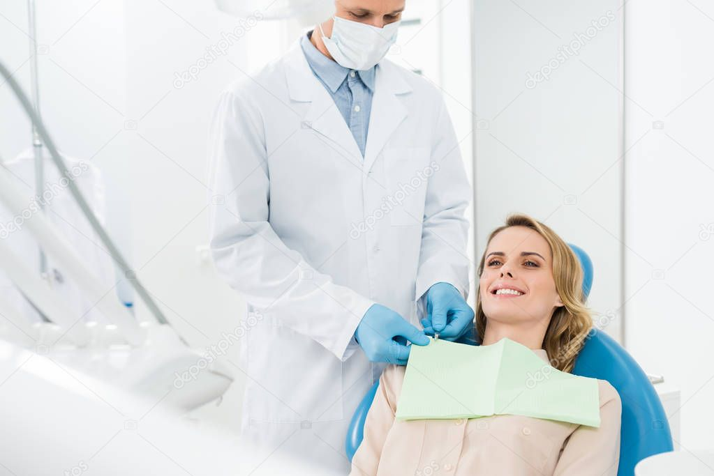 Doctor fixing female patient napkin in modern dental clinic