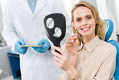Fotografie Patientin, die sich für ein Zahnimplantat entscheidet, schaut in der modernen Zahnklinik in den Spiegel