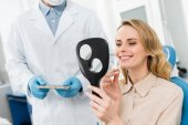 Fotografie Woman choosing tooth implant looking at mirror in modern dental clinic