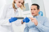 Fotografie Female doctor and patient choosing tooth implants in modern dental clinic