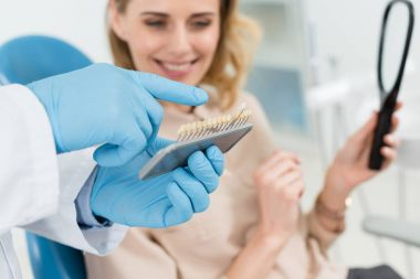 Doctor choosing tooth implants with female patient in modern dental clinic