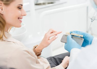 Doctor showing tooth implants to female patient in modern dental clinic