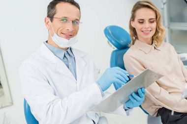 Doctor recording diagnosis while consulting with patient in modern dental clinic