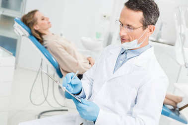 Dentist recording diagnosis while female patient waiting in modern clinic