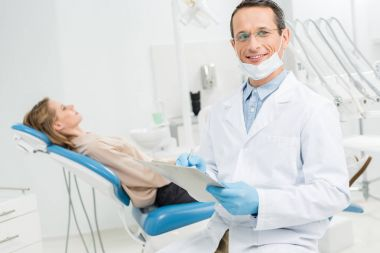 Doctor filling checklist about female patient health in modern dental clinic
