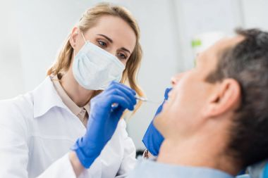 Doctor checking patient teeth with mirror in modern dental clinic