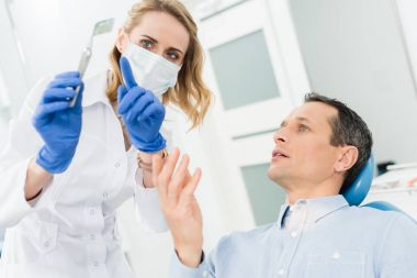 Female dentist showing male patient x-ray in modern dental clinic