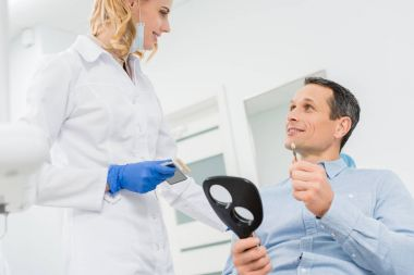Man choosing tooth implant consulting with doctor in modern dental clinic
