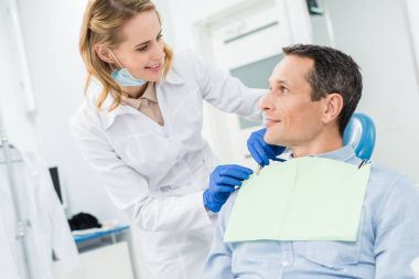 Doctor fixing male patient napkin in modern dental clinic