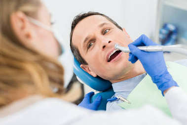 Male patient at dental procedure using dental drill in modern dental clinic