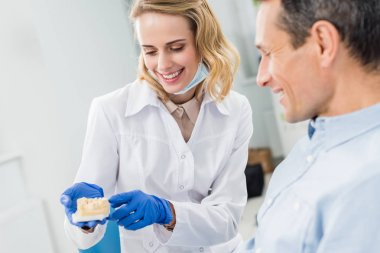 Doctor and patient looking at jaws model in modern dental clinic