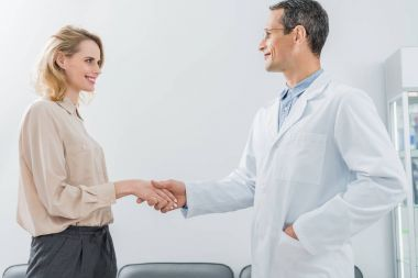 Male doctor and female patient shaking hands in modern dental clinic