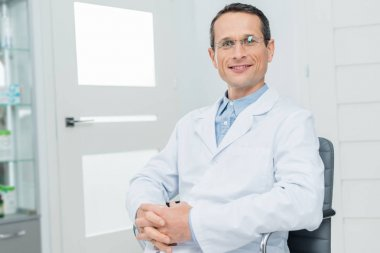 Smiling doctor with clenched hands in modern clinic