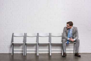 caucasian businessman looking at empty chairs while waiting for job interview