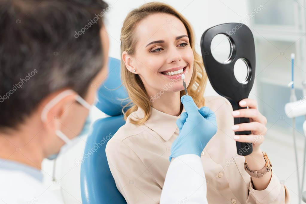 Female patient choosing tooth implant looking at mirror in modern dental clinic
