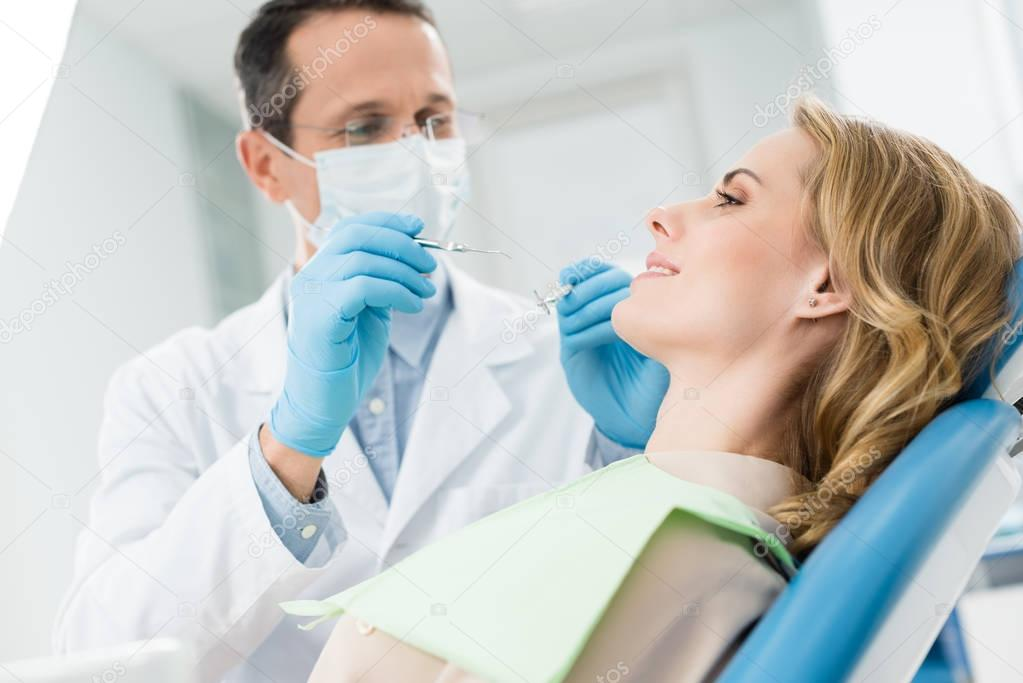 Female patient at dental procedure in modern dental clinic