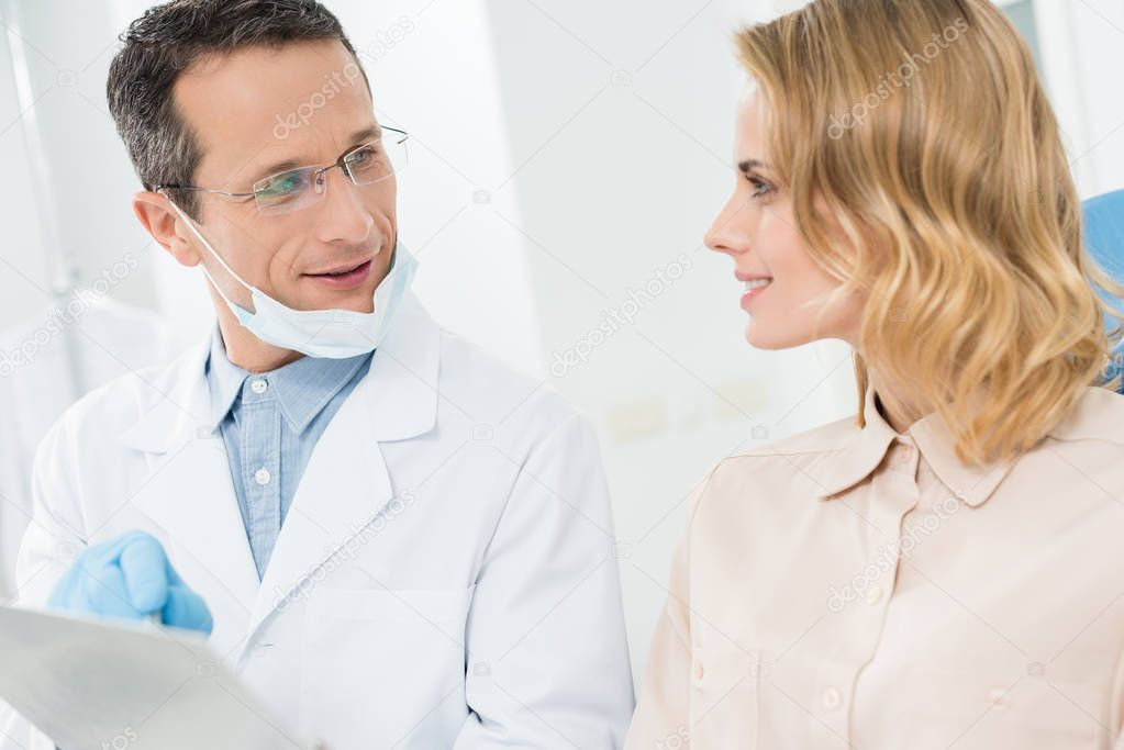 Woman consulting with doctor pointing at clipboard in modern dental clinic