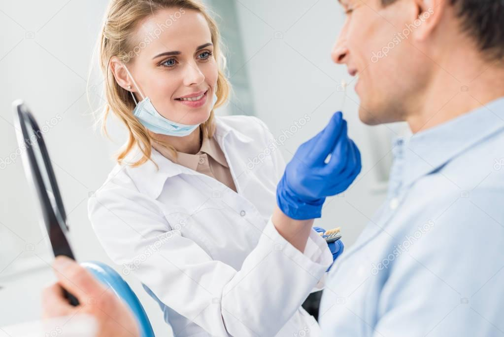 Patient choosing tooth implant looking at mirror in modern dental clinic