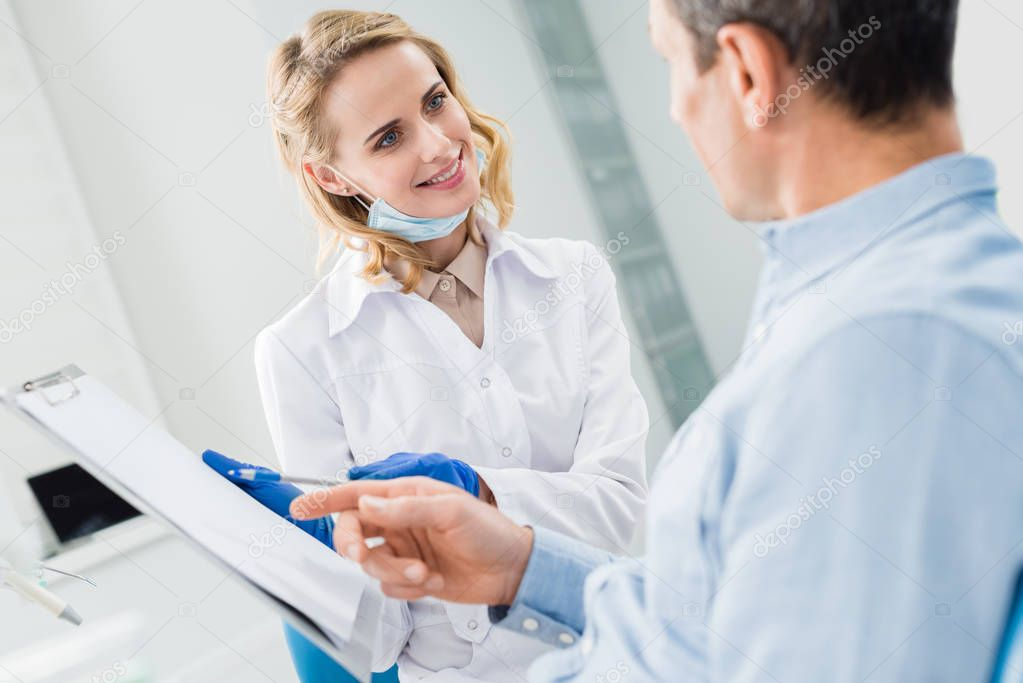 Man consulting with female dentist recording diagnosis in modern clinic
