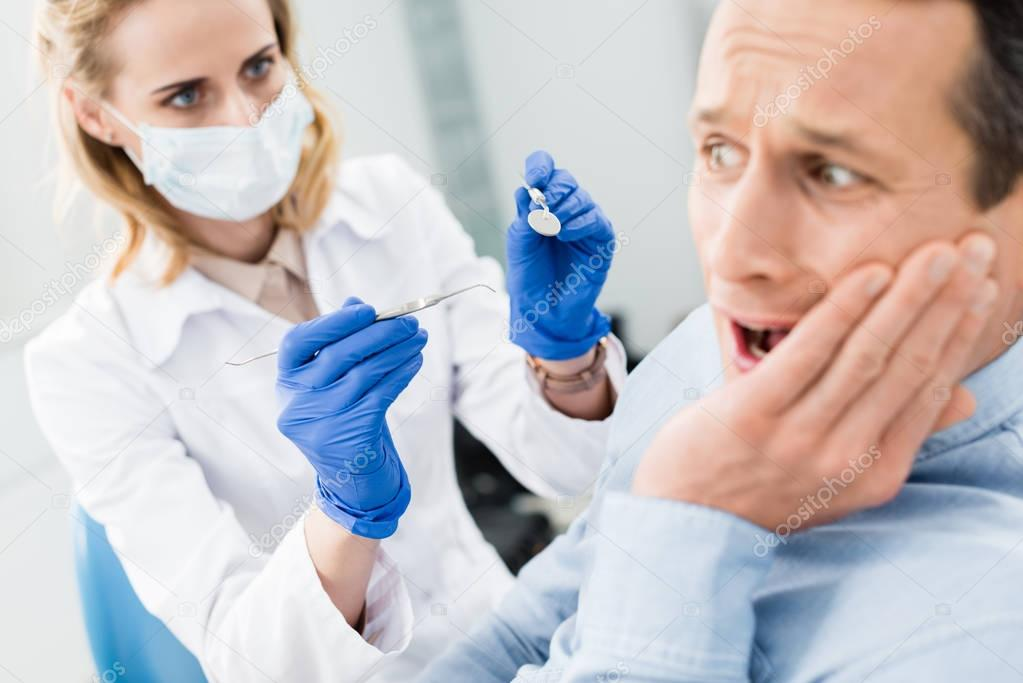 Male patient is afraid of dentist in modern dental clinic