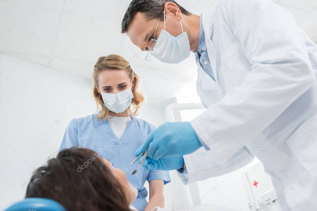 Male dentist and his female assistant checking patient in modern dental clinic
